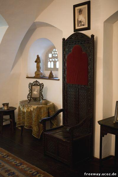 Интерьер замка Bran. Над высоким, деревянным стулом висит портрет королевы Марии