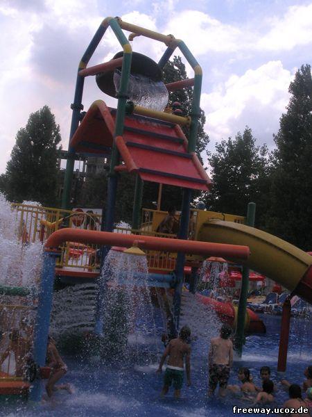 Цветной домик детской площадки с постоянно льющимися и брызгающими струйками водой. На вершине домика бочкой, которая постепенно наполняется водой, а после неожиданно опрокидывается на зазевавшуюся молодежь.