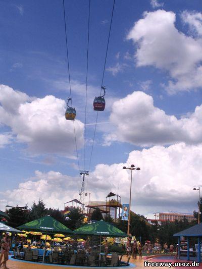 Кабинки подвесной канатной дороги Telegondola пролетающие над аквапарком.