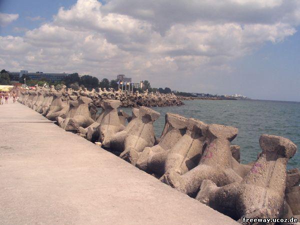 Пирс курорта Mangalia и следующая за ним береговая линия, обложенны большими бетонными ежами – волнорезами.