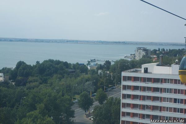 Вид из кабинки подвесной канатной дороги. Озеро Siutghiol, на водной глади которого можно рассмотреть причал и стоящий рядом корабль «Ovidiu».
