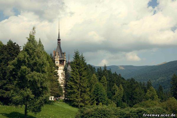 Замок Peles. Вид с торца замка. Центральная башня, утопающая в зелени деревьев